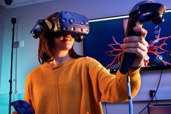 A student in an orange sweatshirt wearing VR goggles stands in front of a blue scientific visualization.