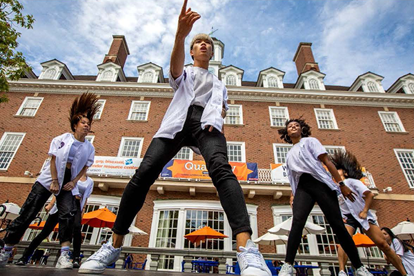 Four students wearing white tops and black pants dance in front of the Illini Union.