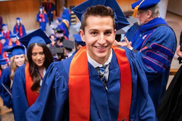 Several students and faculty in blue graduation gowns with orange stoles