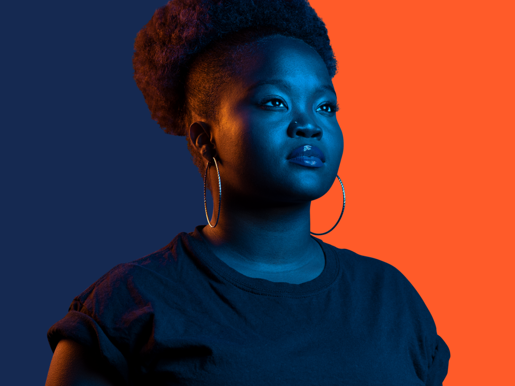 A Black woman stands against a blue and orange backdrop, with orange light against the blue side and blue light against the orange side.
